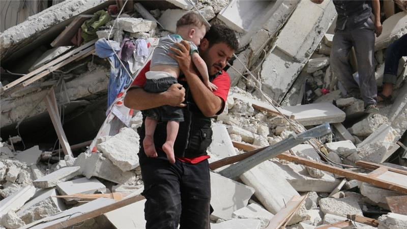 A man carries a wounded child after air strikes on a rebel-held area of Aleppo on Wednesday